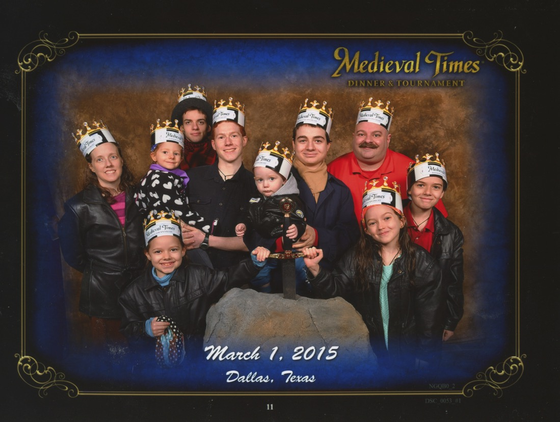 Medieval times Stone Wall Background. Excalibur prop that Bernie, Becket and Jacinta have their hands on. Jen, Bernie, Michael holding Catie, Joseph, Nunzio Holding Becket, Justin, Jacinta and Cross. Bottom Text: 'Dallas, Texas March 1, 2015'